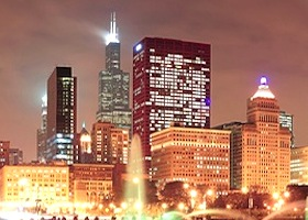 Chicago skyline panorama with skyscrapers and Buckingham fountain in Grant Park at night lit by colo